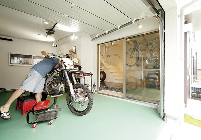玄関スペースとガレージはガラス扉で繋がっている