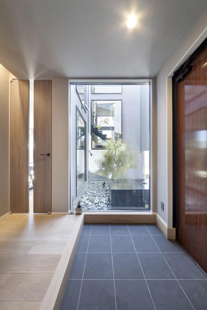 中庭と隣り合わせの玄関も開放的なイメージ